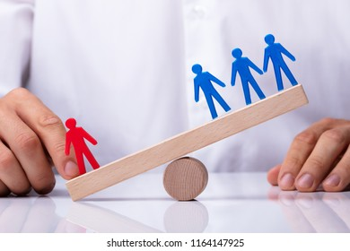 Businessperson's Finger Showing Red Human Figure Competing Against Blue Team On Wooden Seesaw