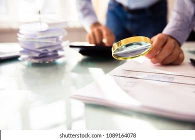 Businessperson's Hand Analyzing Bill Through Magnifying Glass