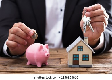 Businessperson's hand holding coin and key over piggybank and house on wooden desk