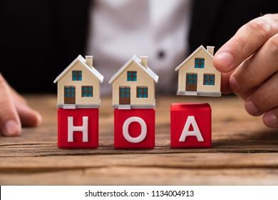 Businessperson's hand placing house model over red HOA blocks on wooden desk