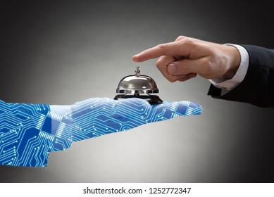 Businessperson's Hand Ringing Service Bell Held By Digital Generated Human Hand On Grey Background