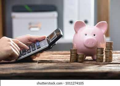 Businessperson's Hand Using Calculator With Stacked Coins And Piggy Bank On Wooden Desk