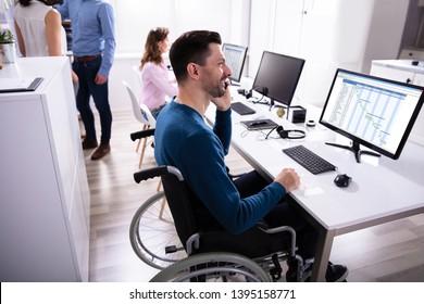 Businessperson's Talking Mobilephone Analyzing Gantt Chart On Computer Over Desk