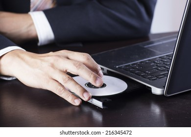 Business's hand holding Disk insert to laptop computer