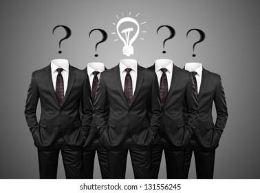Businesssman with idea standind between other businessmen having questions instead of heads