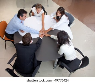 businessteam in an office with hands together for teamwork
