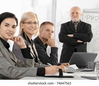 Businessteam sitting at training, smiling at camera, experienced businessman standing with arms folded in background.?