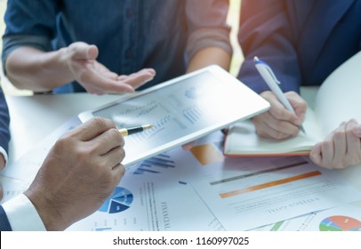 Businessteam use a tablet analyzing graphs with secretary take notes.