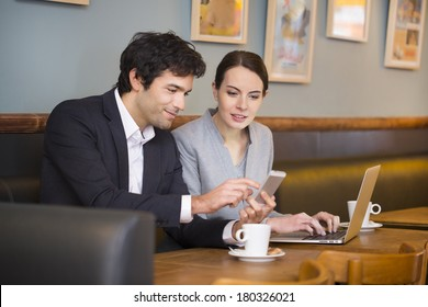Business-team working on laptop at coffee bar, looking a mobile phone