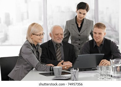 Businessteam working together, mid adult businesswoman showing project on computer to senior executive, colleagues watching.?