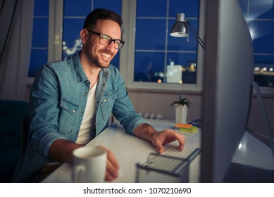 Business,technology and people concept-man with laptop working late at night from home office.