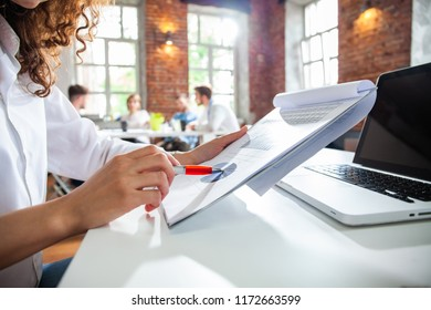 Businesswoman or accountant hand holding pencil working on calculator to calculate financial data report, accountancy document and laptop computer at office, business concept