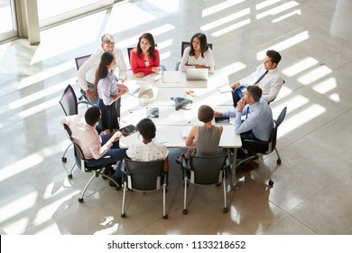Businesswoman addressing colleagues at table, elevated view