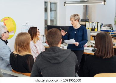 Businesswoman addressing a group of colleagues in a large open plan office as they sit grouped around in chairs viewed from the rear