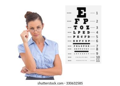 Businesswoman adjusting her glasses against eye test