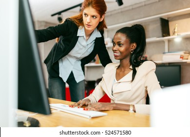 Businesswoman advising colleague in office during work