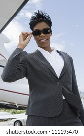 Businesswoman with airplane in background