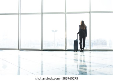 Businesswoman in airport with laggage looking at terminal panoramic windows
