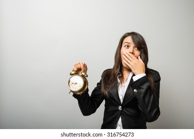 businesswoman with an alarm clock yawning