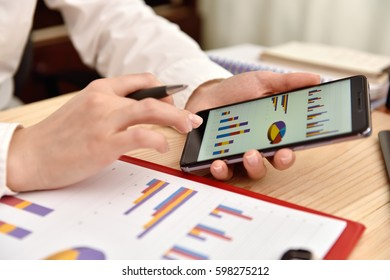 Businesswoman Analyzing Chart On Cellphone. Close Up