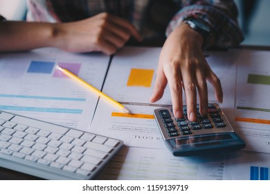 Businesswoman analyzing investment charts with calculator for financial data analyzing counting. Business financial analysis and strategy concept.