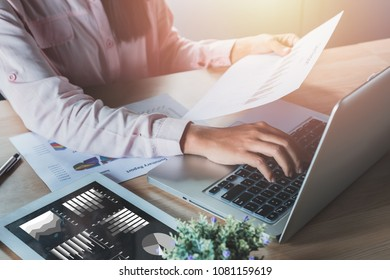 Businesswoman analyzing investment charts with laptop computer on office desk table.Financial Report Revenue Statistical Accounting Concept.