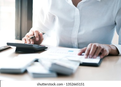 Businesswoman analyzing investment charts and pressing calculator buttons over documents. Accounting Concept