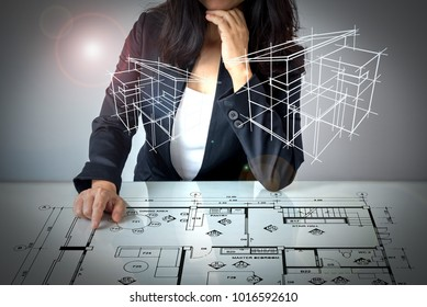 Businesswoman (Architect / Interior designer) working with lay out plan on modern futuristic virtual table & 3D home