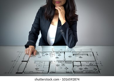 Businesswoman (Architect / Interior designer) working with lay out plan on modern futuristic virtual table