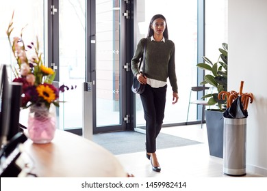 Businesswoman Arriving For Work At Office Walking Through Door