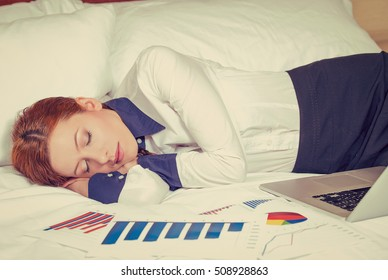 Businesswoman asleep on the bed, hotel or domestic room. Tired employee taking a nap. Long working hours