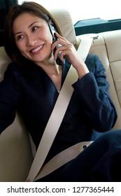 Businesswoman in backseat of car wearing seatbelt on mobile phone