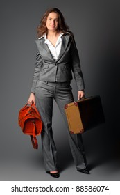 A businesswoman with a bag and a suitcase. On a gray background.