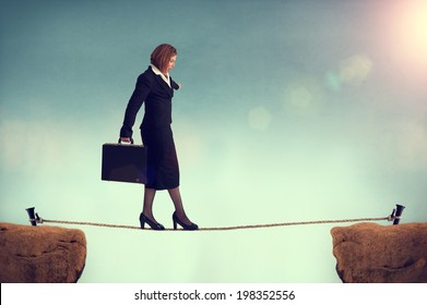 businesswoman balancing on a tightrope conquering adversity concept