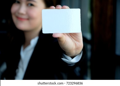 Businesswoman in black costume show business card or name card, woman holding  credit card in hand, female is introduced by giving blank card