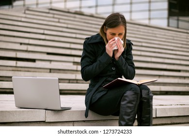 Businesswoman blowing nose while working outdoor.Toned image.