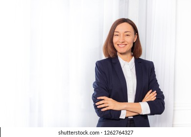 Businesswoman in blue suit jacket with arms folded