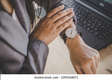 businesswoman boss checking the time on watch at her office waiting for partners coming late