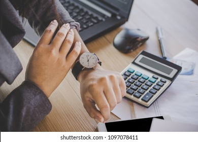 businesswoman boss checking the time on watch waiting for partners coming late sitting at her desk office