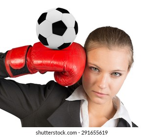 Businesswoman in boxing gloves with soccer ball looking at camera on isolated white background