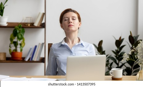 Businesswoman breathing, stretching shoulders after hard work feeling discomfort at office desk work. Young tired woman take minute pause keeping eyes closed. Uncomfortable chair, overwork on laptop