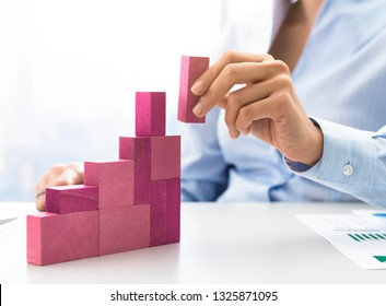 Businesswoman building a growing financial chart with wooden pieces, she is adding the last block, development and strategy concept