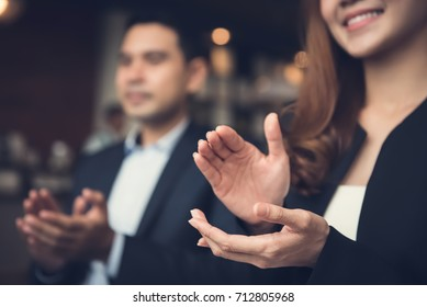 Businesswoman and businessman applauding an agreement during a business meeting in cafe
