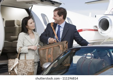 Businesswoman and businessman arrived to an airfield