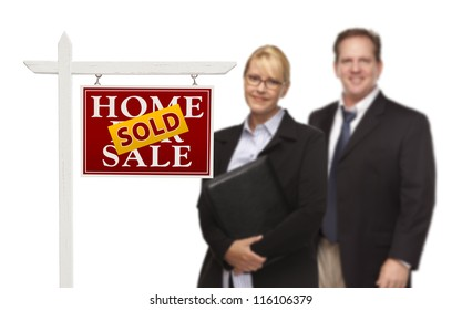 Businesswoman and Businessman Behind Sold Home For Sale Real Estate Sign Isolated on a White Background.