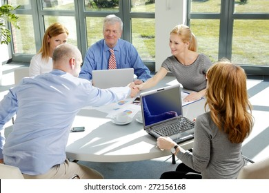 Businesswoman and businessman closing the deal and shaking hands. Group of sales people sitting at desk in front of laptop and making agreement. Working at office.