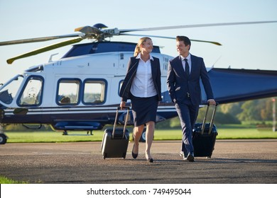 Businesswoman And Businessman In Discussion As They Walk Away From Helicopter