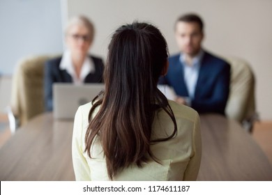 Businesswoman and businessman HR manager interviewing woman. Candidate female sitting her back to camera, focus on her, close up rear view, interviewers on background. Human resources, hiring concept
