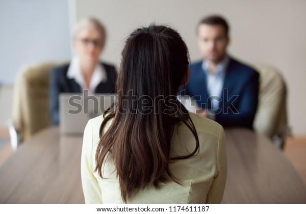 Бизнесвумен и бизнесмен HR менеджер интервью женщина. Кандидат женщина сидит назад к камере, сосредоточиться на ней, закрыть вид сзади, интервьюеры на заднем плане. Людские ресурсы, концепция найма