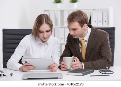 Businesswoman and businessman looking at tablet. Office at background. Concept of cooperation.